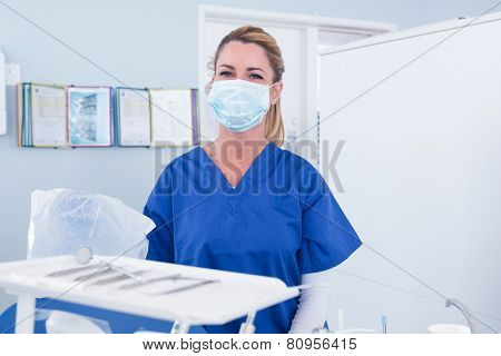 Dentist in mask behind tray of tools at the dental clinic