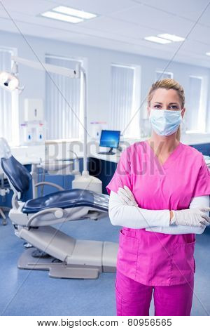 Dentist in pink scrubs standing with arms folded at the dental clinic