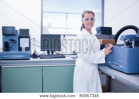 Young chemist with safety glasses doing scientific research in laboratory