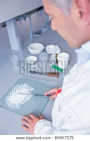 Biochemist standing while preparing some medicine in laboratory