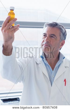 Smiling scientist in lab coat holding a chemical bottle in laboratory