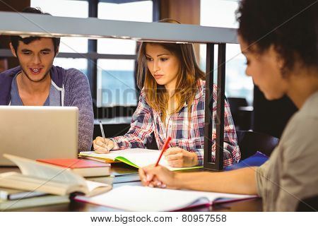 Serious young classmates working together in library