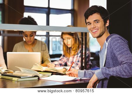 Student looking at camera with his classmates behind him in library