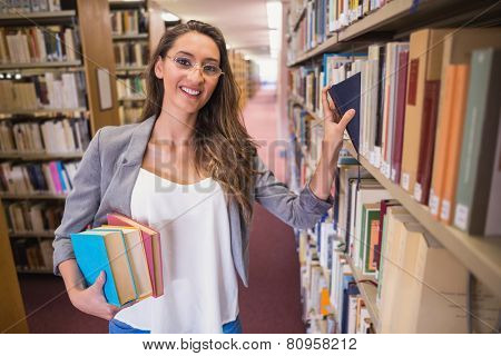 Pretty student picking out a book in library at the university