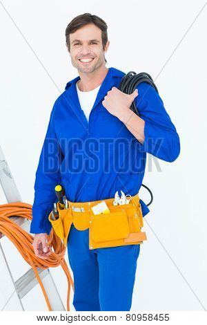 Portrait of happy electrician with wires over white background