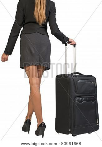 Cropped image of businesswoman with wheeled travel bag makes step forward, back view