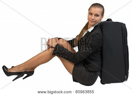 Businesswoman sitting next to side view suitcase, hugging her knees, looking at camera