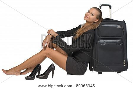 Businesswoman with her shoes off sitting next to front view suitcase