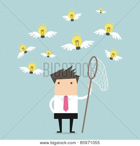 Businessman trying to catch a light bulb idea