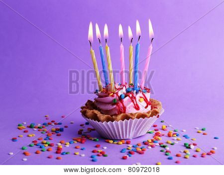 Birthday cup cake with candles and colorful sparkles on purple background