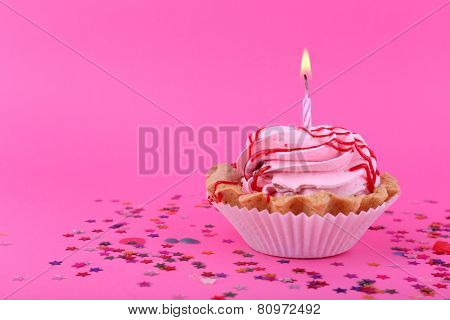 Birthday cup cake with candle and colorful stars on pink background