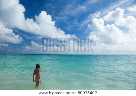 Little girl enjoys summer day at the tropical beach.