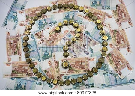 The question mark in the circle, made of coins on the background of banknotes