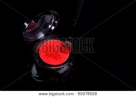 Red Eyeshadow With Brush and Loose Powder on Black Background