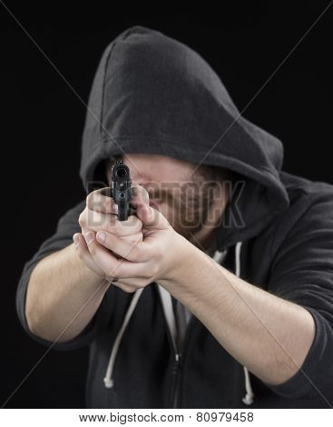 Young Man in Hood Holding Gun