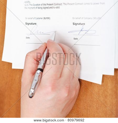 Businessman Signs An Agreement By Silver Pen