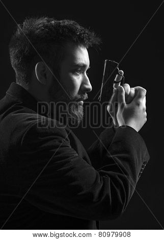 Serious Young Man Holding Gun Facing Right