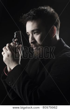 Goatee Man in Black Suit Holding Small Gun