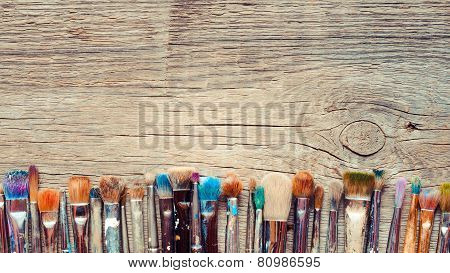 Row Of Artist Paintbrushes Closeup On Old Wooden Rustic Background