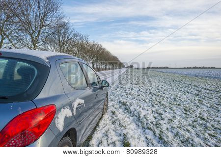 Car parked along a snowy road in winter