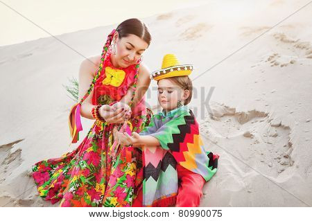 Toned photo of happy Mom and son dressed in Mexican clothes play sand