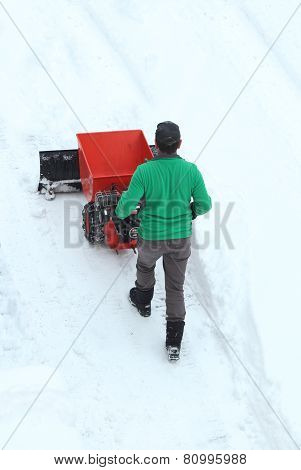 Man Moving A Engine Driven Snowplow