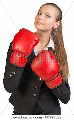 Businesswoman wearing boxing gloves, looking ahead and upwards