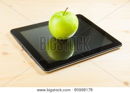 Green Apple On Digital Tablet Pc On Wood Table