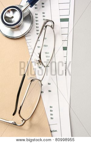 A statoscope and glasses on papers from above
