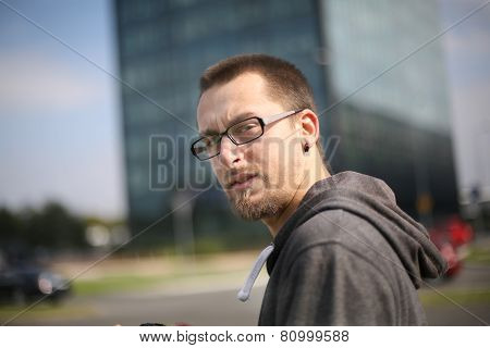 A Young Man With Eyeglasses Walking On The Street
