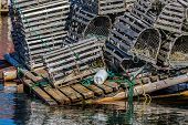 stock photo of lobster trap  - Old wooden lobster traps with buoys and rope on a wharf in Newfoundland - JPG