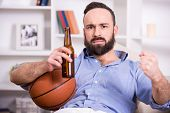 image of couch potato  - Young man with basketball and beer while watching the game - JPG