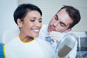 stock photo of dentist  - Male dentist examining womans teeth in the dentists chair - JPG