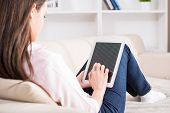 foto of couch  - Back view of smiling young woman is using tablet while lying on couch at home - JPG