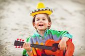 stock photo of ukulele  - Toned photo of Little happy smiling boy plays his guitar or ukulele - JPG