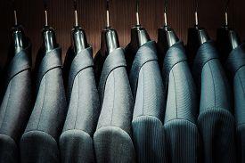 stock photo of jacket  - Row of men suit jackets on hangers - JPG