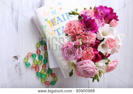 Beautiful fresh spring flowers with stack of books, top view