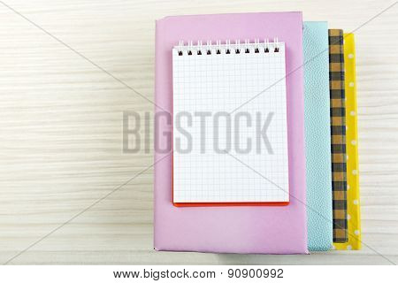 Notebook on top of pile of books and magazines on wooden background