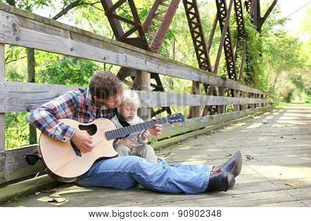 Father And Young Child Playing Guitar Outside At Park