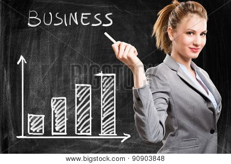 Smiling woman showing a positive business trend on a blackboard