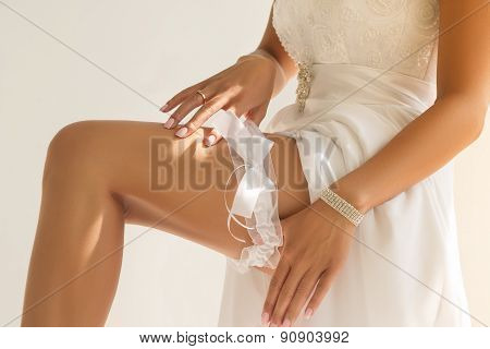 Close-up Of Bride's Hands Putting Garter