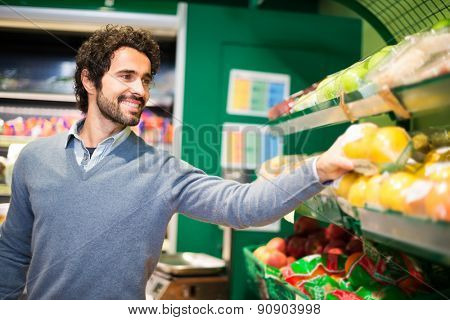 Smiling young man picking up vegetables in a grocery store