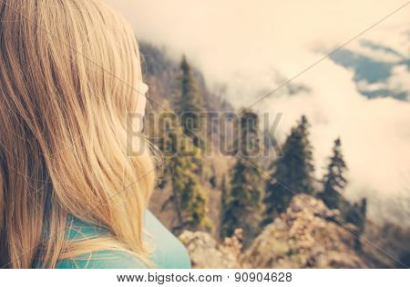 Young Woman relaxing outdoor on mountain summit with aerial view