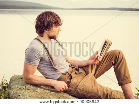 Young Man reading book outdoor with scandinavian lake and mountains on background