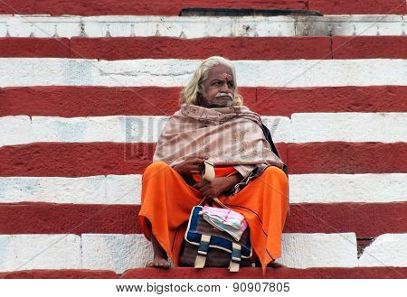 Indian Sadhu Sits On The Steps Of The Kedar Ghat Near Sacred River Ganges In Varanasi