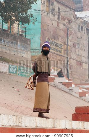 Indian Man Stands On The Steps Of Ghat Near Sacred River Ganges In Varanasi