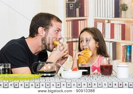 Fun loving dad having breakfast with small daughter