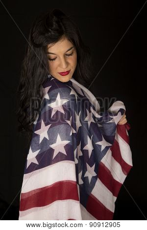 Beautiful Woman With American Flag Draped On Shoulder Looking Down