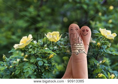 Conceptual Family Finger Art. Couple Is Embracing And Holding Birthday Cake With Candles