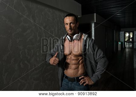Mature Man Listening Music In Modern Corridor